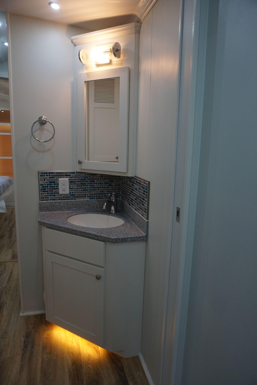 Corner Solid Surface Lavatory Top with Custom Medicine Cabinet & Tile Backsplash